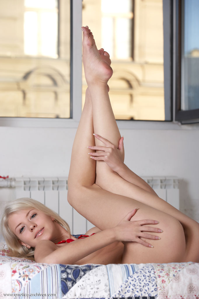 Blonde beauty Barbara shows off her puffy nipples and shaved pussy on top of the bed