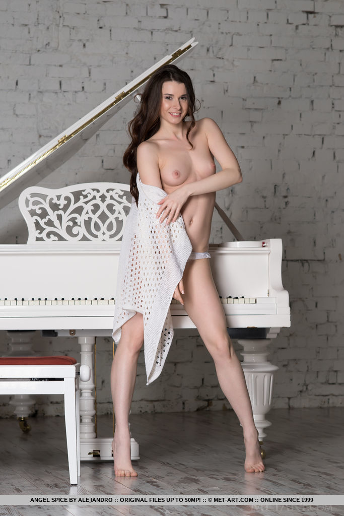 Gorgeous Angel Spice displays her delectable body by the piano.