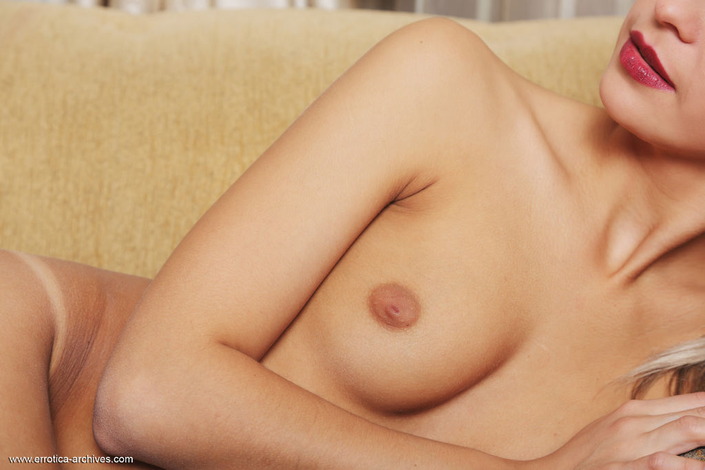 Leonie flaunts her small, puffy nipples and sweet ass on the sofa.