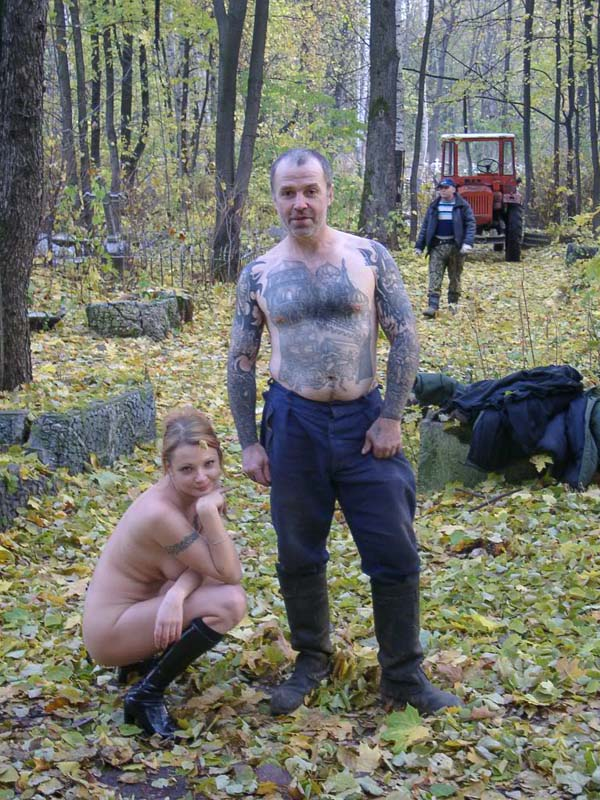 Naked blonde posing with cemetery workers