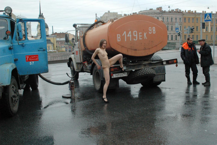 Naked young girl posing with workers