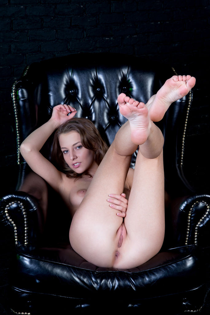 Nikia strips on the chair baring her delectable pussy.