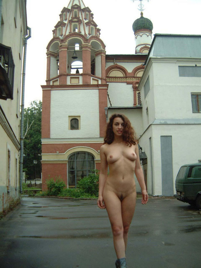 Russian girls walks in boots behind the church