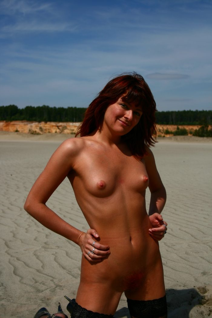 Russian redhead girl posing in stockings on the sand