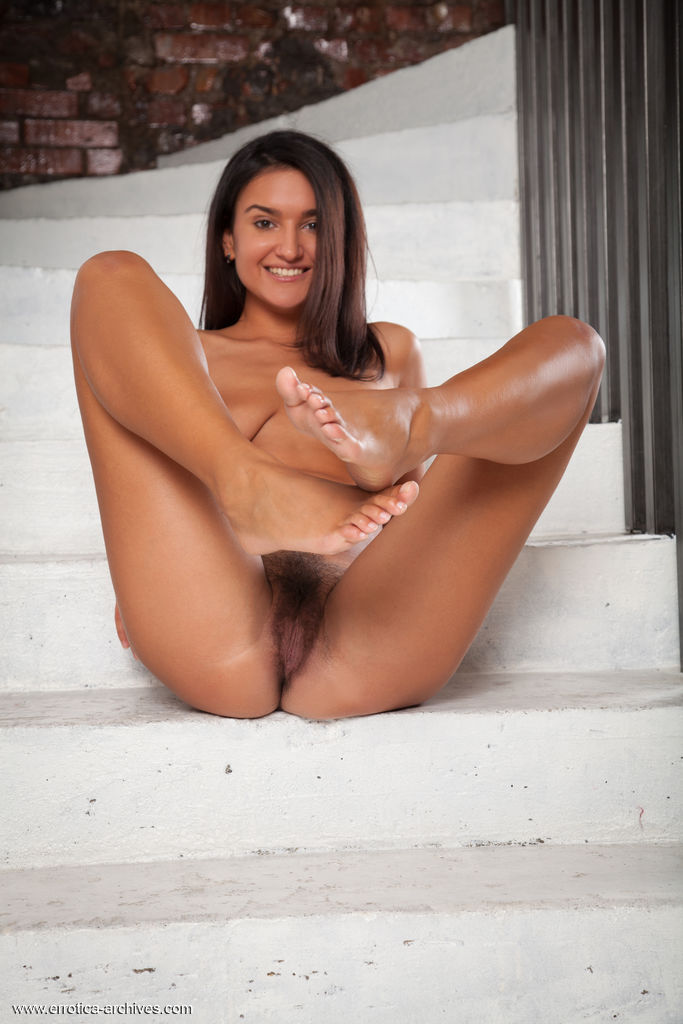 Sanita bares her gorgeous tits and hairy pussy on the stairs.