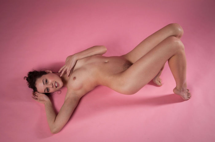 Smiling girl Uliana shows not-shaved pussy in pink studio
