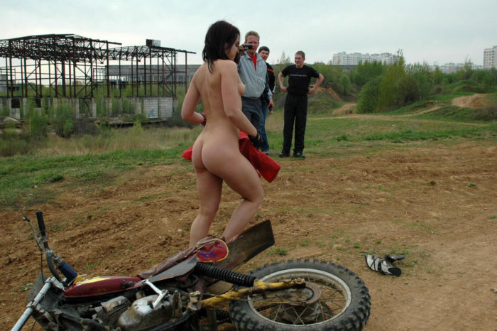 Smiling girl gets naked at motocross field
