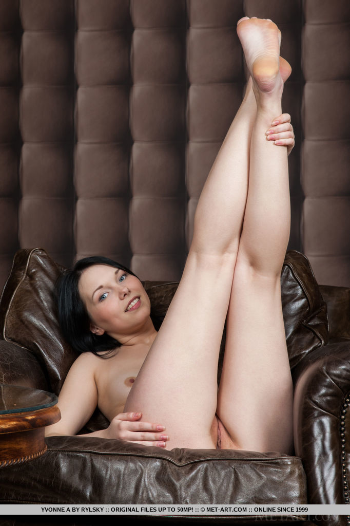 Yvonne A strips and poses confidently on the sofa with her legs wide open, revealing her pink and smooth asset.