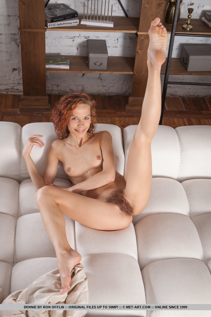 Dennie spreads her legs wide open as she bares her unshaven pussy on the couch.