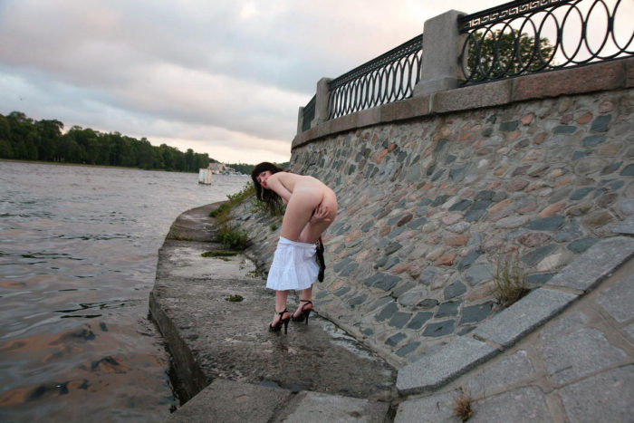 Girl Mila S takes off her clothes on the river bank