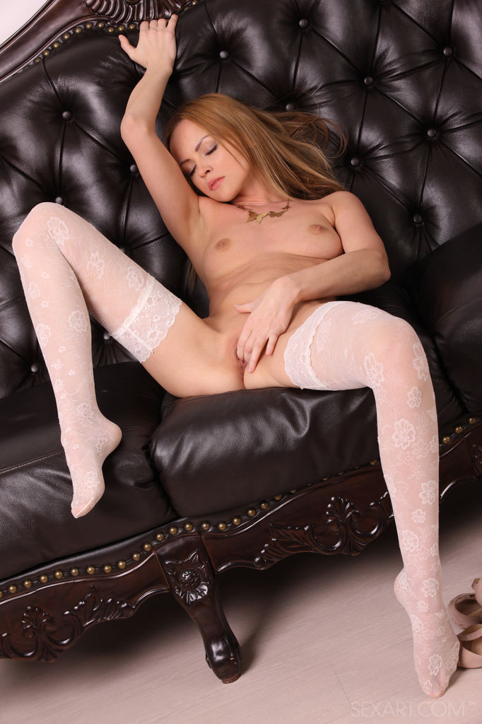 Lidia B shows off her delicate petite body clad delightfully clad in white matching lingerie with lace garter belt that hugs her sensual hips and thigh-high stockings.