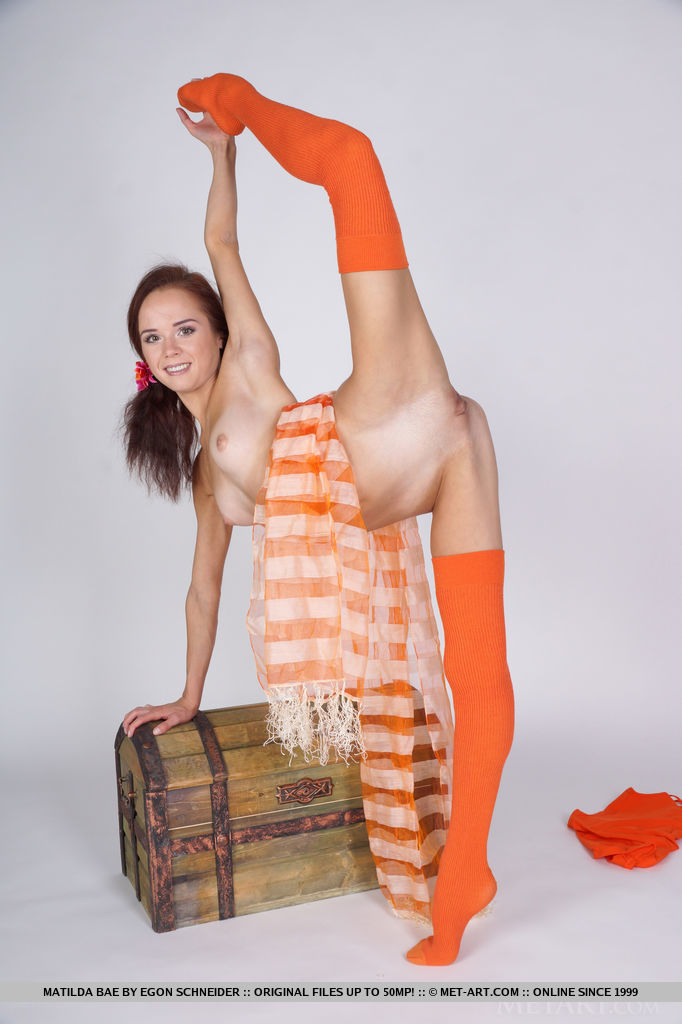 Matilda Bae showing off her flexible legs with bright orange thigh-high stocking and wide open poses