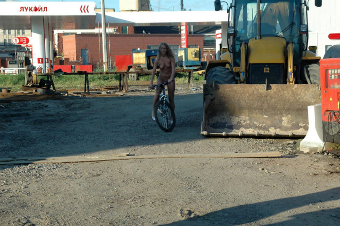 Naked blonde on bicycle at city center