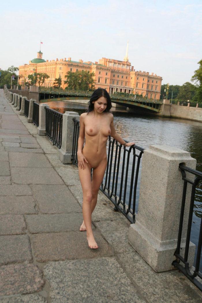 Sweet brunette posing naked at river embankment