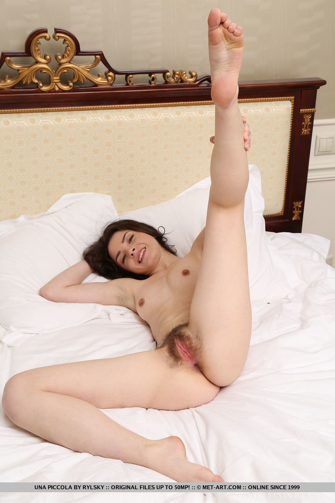 Una Piccola shows off her creamy naked body and bares her unshaven pussy on the bed.