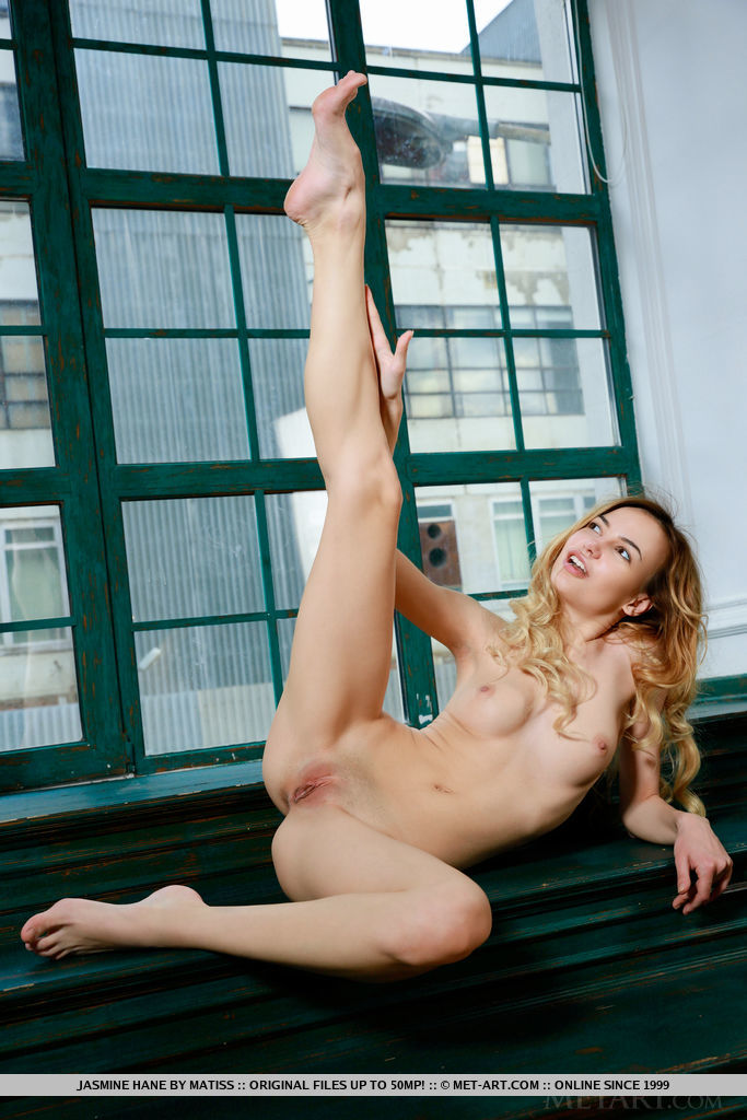 Jasmine Hane strips by the window baring her tight body and smooth pussy.