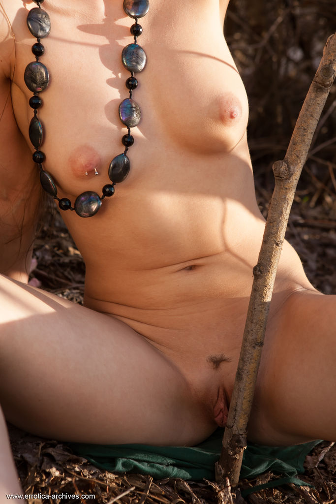 Subil A bares her pierced nipple and trimmed pussy outdoors.