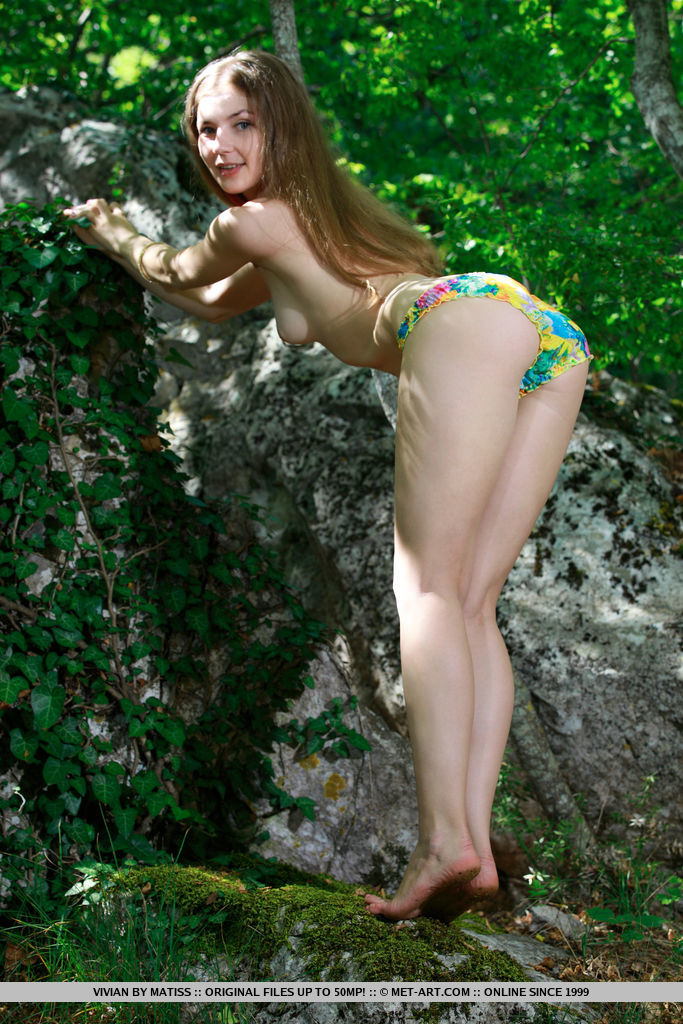Vivian strips in the forest baring her creamy, slender body and pink pussy.