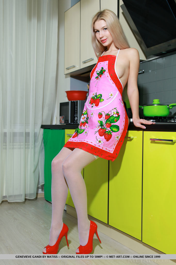 A sexy and naughty Genevieve Gandi, naked in the kitchen except a pink apron, white thigh-high stockings, and red stilettos.