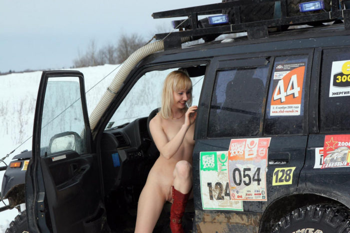 Blonde girl is posing by the safari car