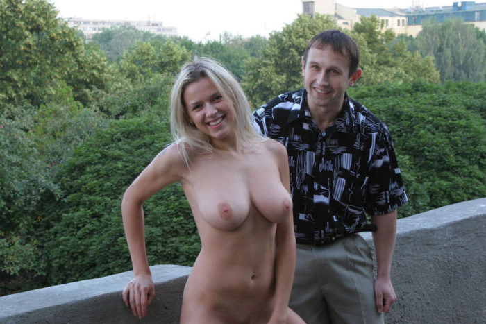 Blonde without clothes posing with a stranger at city center
