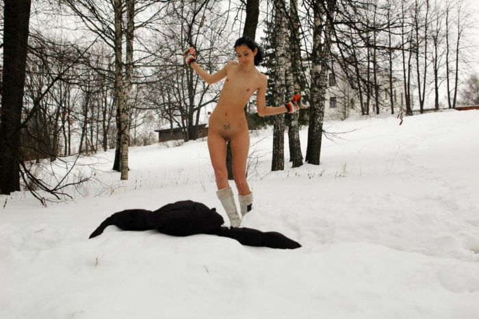 Brunette with slender body plays with a snow