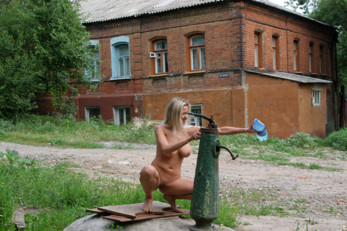 Busty blonde draws water from a well