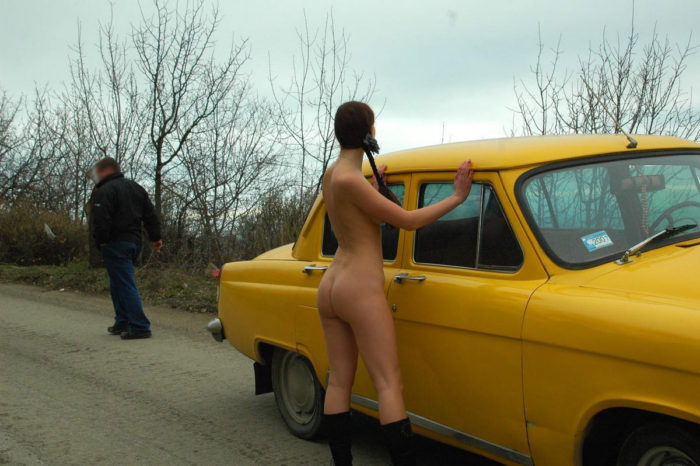Huge-titted female next to a yellow retro car
