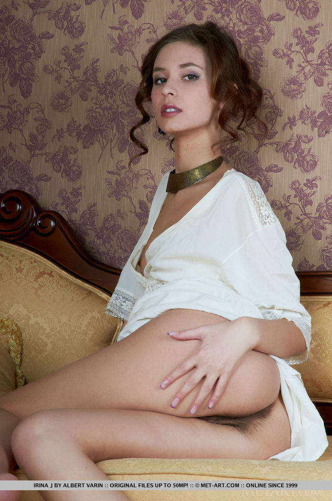 Irina J carefully strips off her clothes on top of the couch until she reveals her decadent, unshaven pussy.