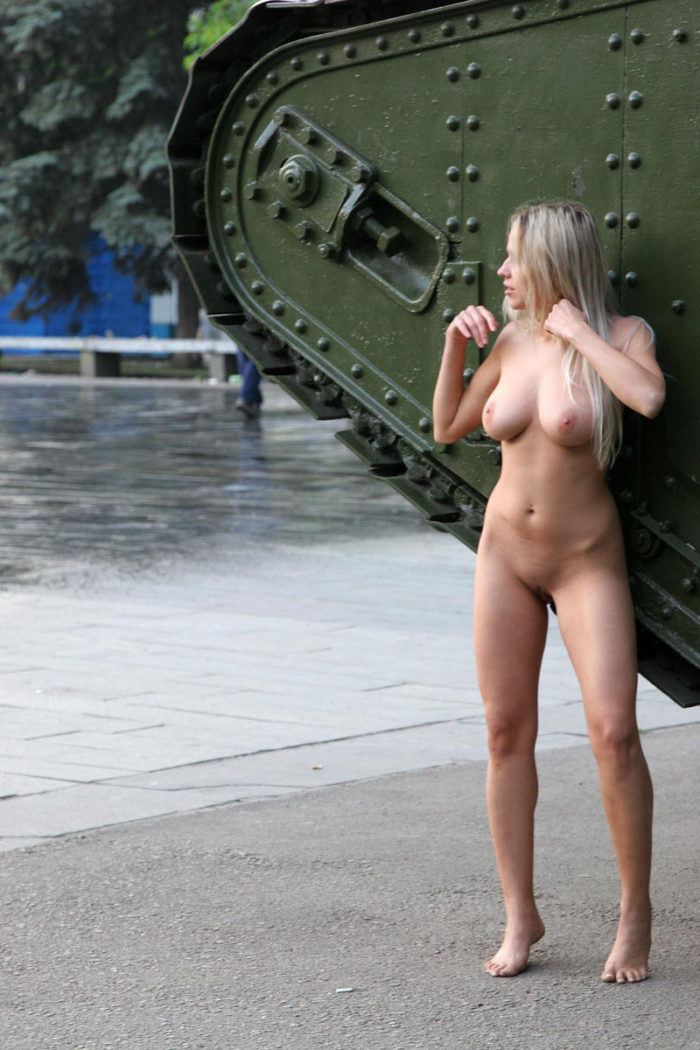 Naked girl posing next to a tank in the town square