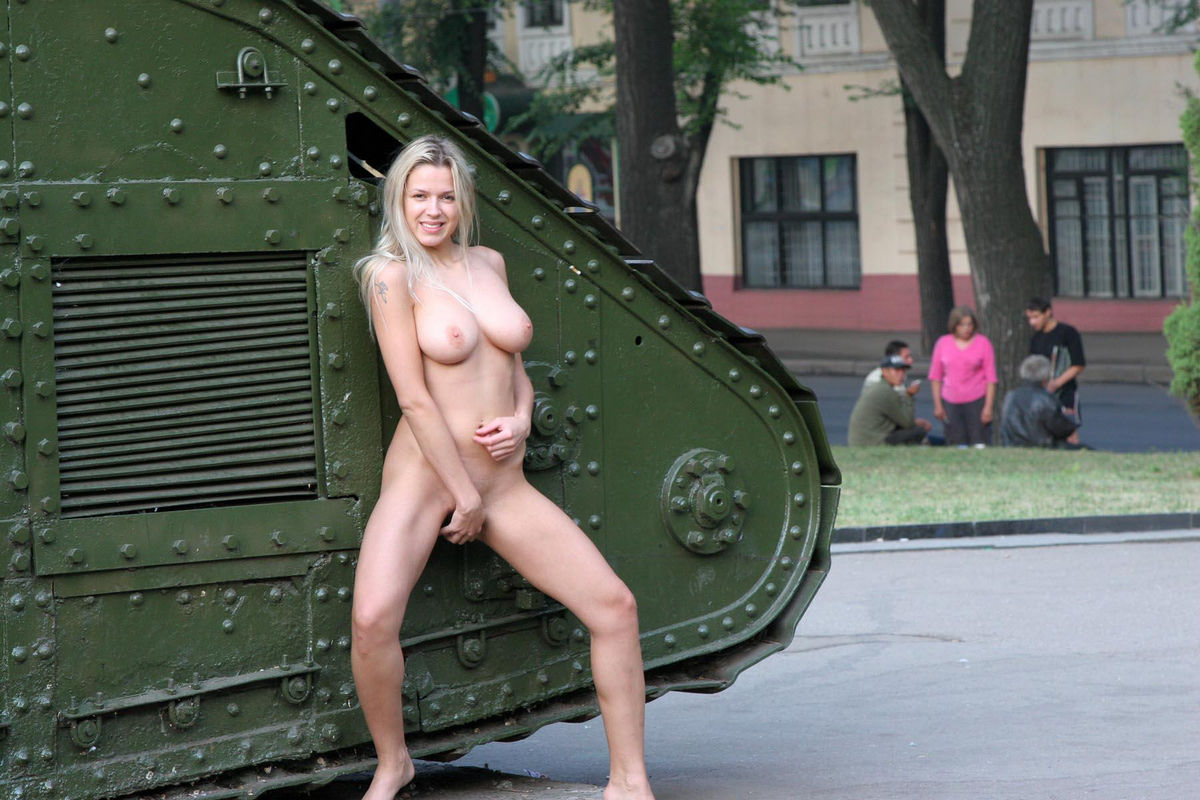 Naked girl posing next to a tank in the town square ...