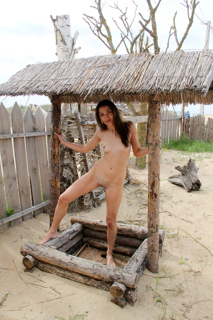 Naked girl swinging on a swing on the beach