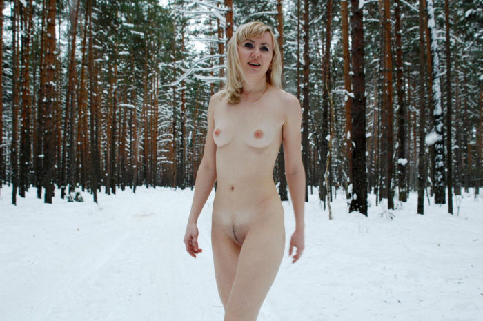 Nude blonde playing with snow in the forest