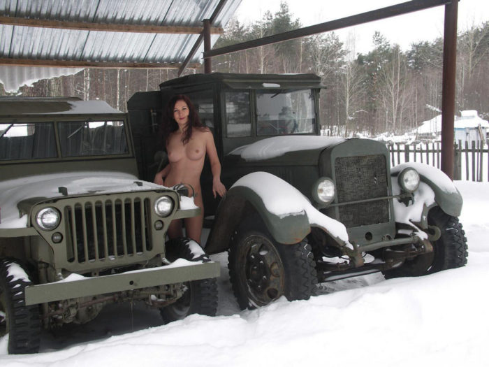 Nude lady with a tat in a museum of old cars