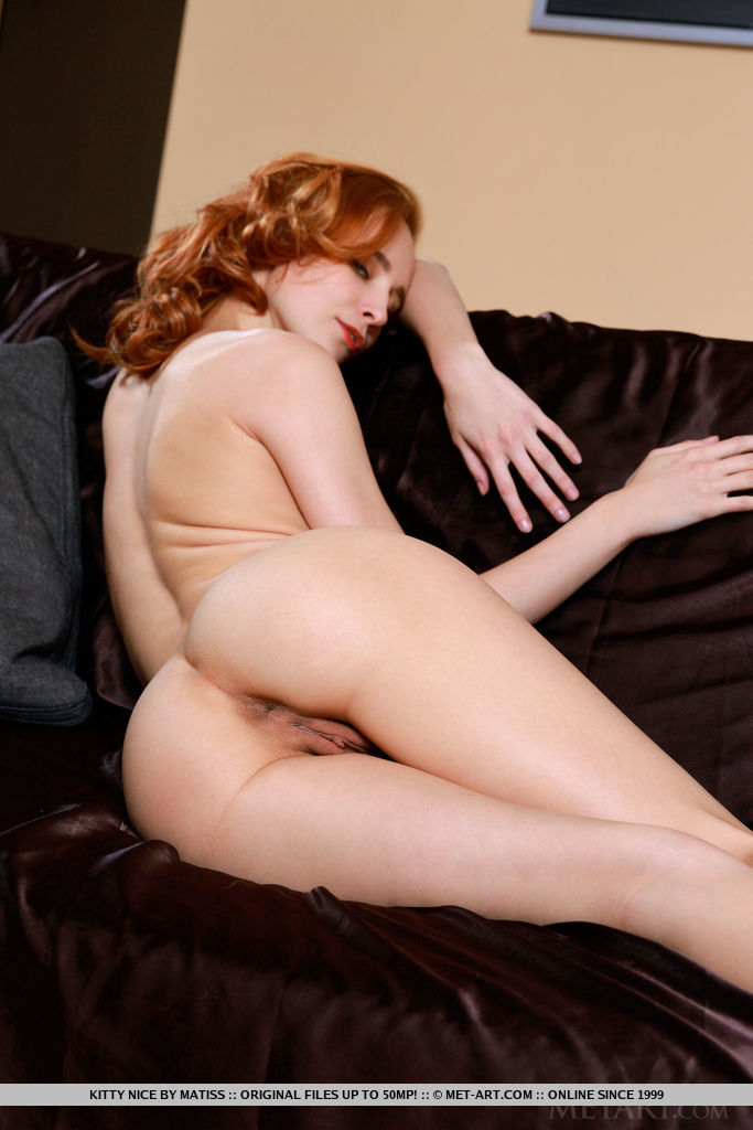 Redhead Kitty Nice displays her amazing physique on the couch.