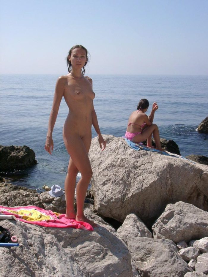 Sexy lady rests with spread legs on sea stones