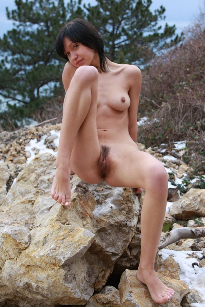 Short-haired brunette shows meaty pussy on the rock