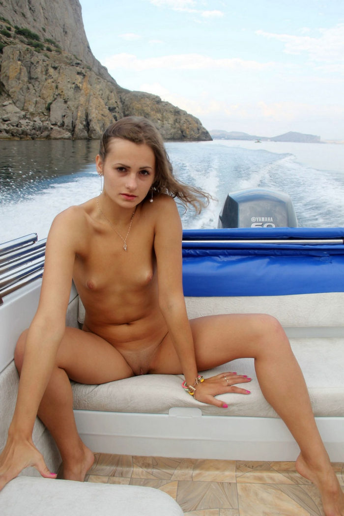 Small-titied girl spreads legs on boat