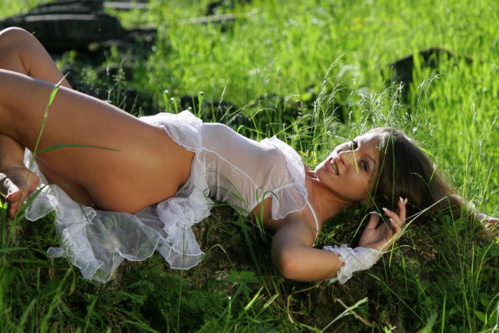 Smiling babe in sexy transparent dress in the park
