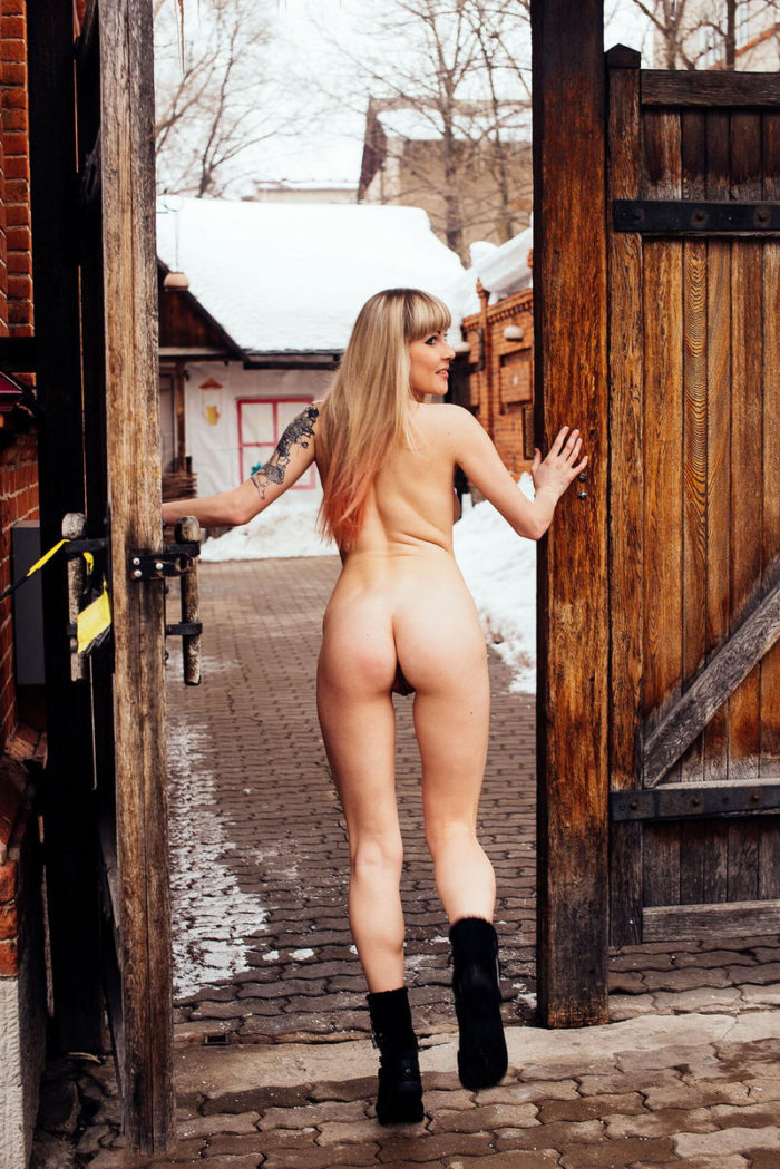 Tattooed blonde with gorgeous body near restaurant