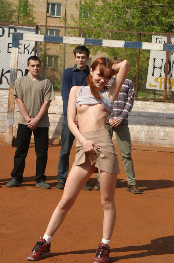 Totally nude damsel on the football ground with strangers