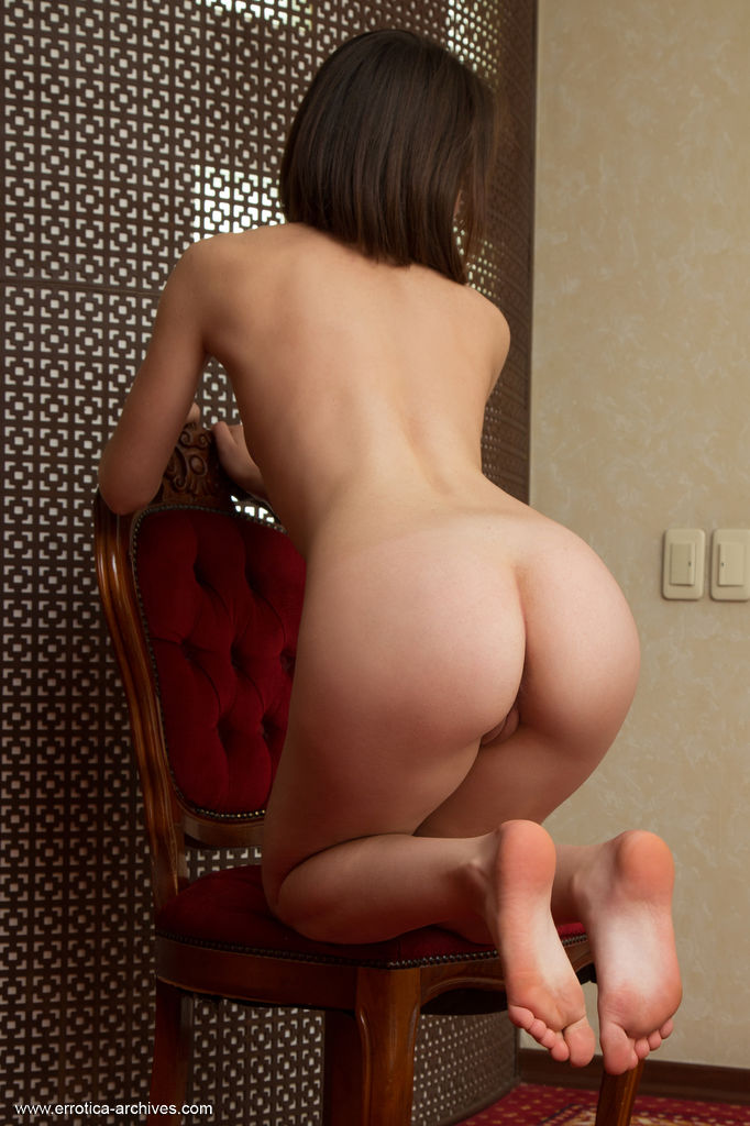 Una Piccola shows off her nubile body and smooth pussy on the chair.