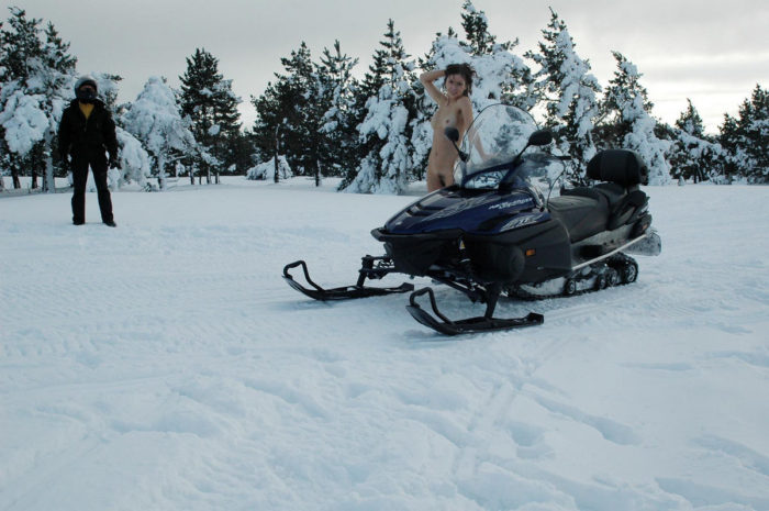 A girl without clothes posing on a snowmobile