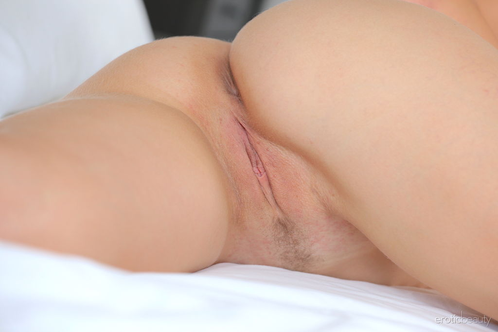 Alluring Genevieve Gandi strips on the bed baring her sweet pussy.