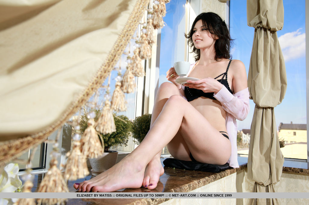 Elizabet enjoying a cup of coffee in her sexy black lingerie that compliments her smooth, porcelain skin