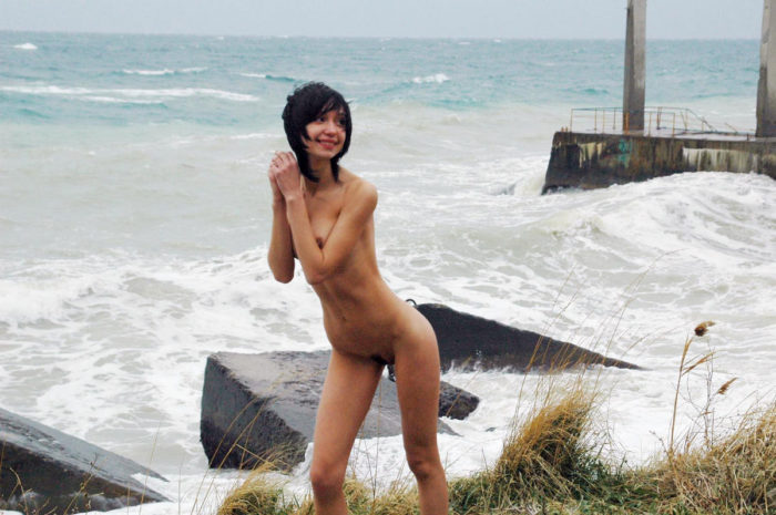 Girl posing next to the stormy sea