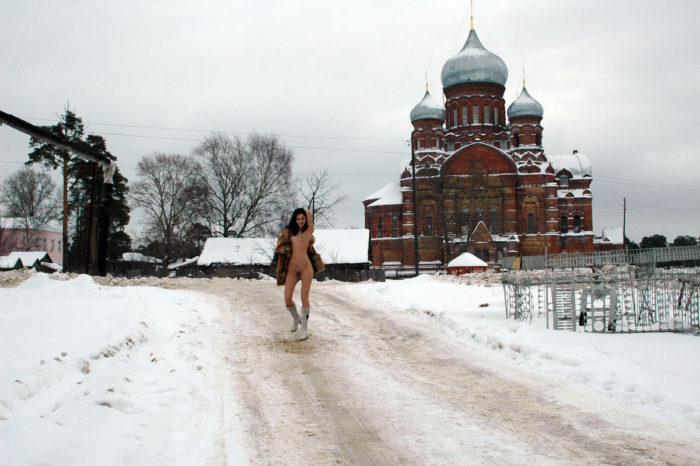 Lovely teen undresses in front of an old church