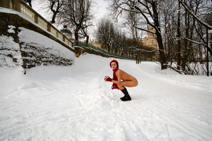 Naked girl in a red beret in a winter park