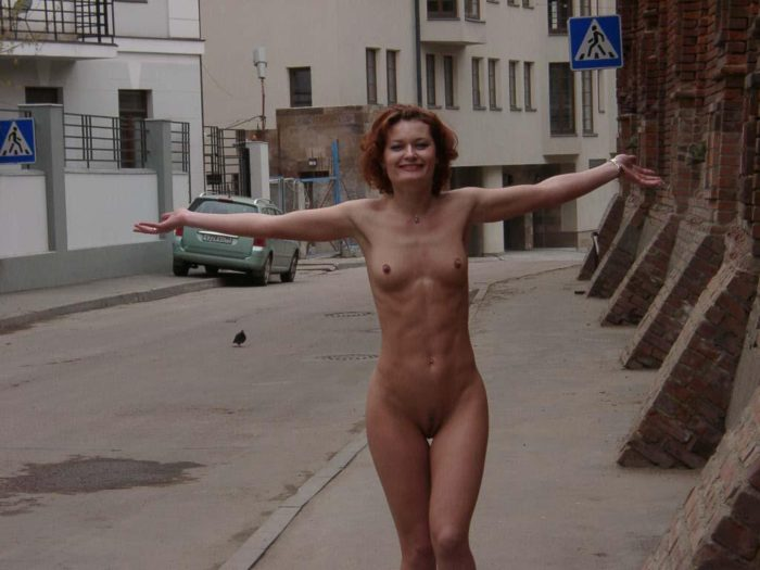 Naked redhead with sporty body on the streets