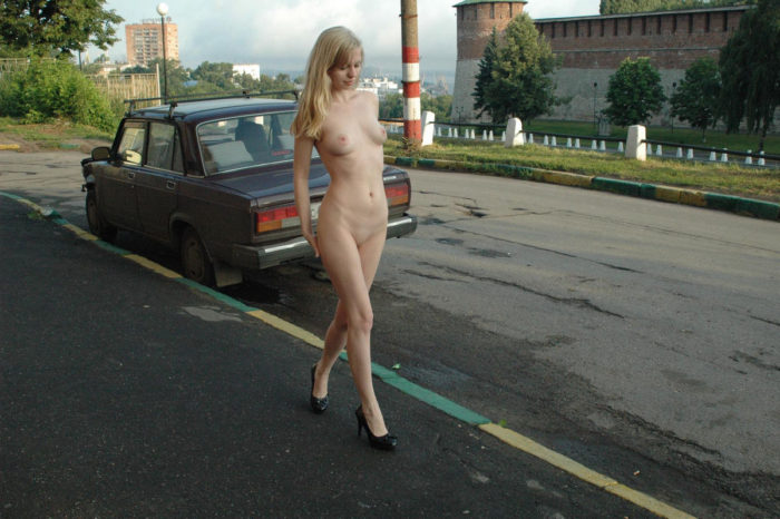 Nude blonde posing at city center